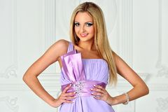 Beautiful blonde woman in violet gown. Royalty Free Stock Image