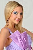 Beautiful blonde woman in violet gown. Stock Image