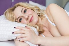 Beautiful blonde woman wakes up in her bed in the morning. stock images