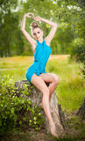 Beautiful blonde woman wearing blue dress posing on a stump in a green forest Royalty Free Stock Photos