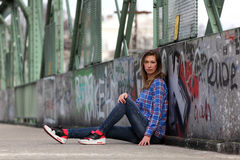 Beautiful blonde woman wearing casual fashion. Young woman with plaid blouse and sneakers sitting on a bridge royalty free stock image