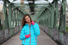 Beautiful blonde woman wearing casual winter fashion. Young woman with jacket and pink gloves on a bridge Stock Photography