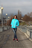 Beautiful blonde woman wearing casual winter fashion. Young woman with jacket and pink gloves on a bridge stock images