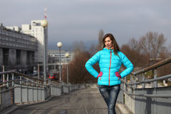 Beautiful blonde woman wearing casual winter fashion. Young woman with jacket and pink gloves on a bridge stock image