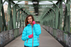 Beautiful blonde woman wearing casual winter fashion. Young woman with jacket and pinkg gloves on a bridge Royalty Free Stock Photos