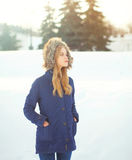 Beautiful blonde woman wearing a coat jacket with hood over snow in winter Royalty Free Stock Photography