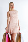 Beautiful blonde woman wearing dress walking holding fresh buyings. In coloured paper bags. Shopping, consumerism, gifts and present, boutique visiting or stock photos