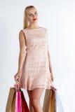 Beautiful blonde woman wearing dress walking holding fresh buyin Stock Photos