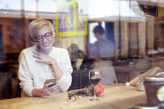 Beautiful blonde woman wearing eyeglasses messaging by mobile phone in cafe. Got a love message. Present box and rose flowers on w Royalty Free Stock Photography