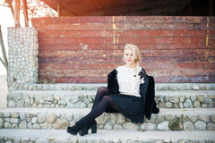 Beautiful blonde  woman wearing fashionable. Beautiful blonde young woman wearing fashionable clothes sitting on stairs Royalty Free Stock Photography