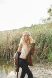 Beautiful blonde woman wearing flared jeans, a white lace top and a brown jacket, posing on the lake. Hippie, Boho Style. Baby`s face model Royalty Free Stock Image