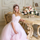 Beautiful blonde woman wearing gorgeous dress and crystal crown posing in luxury classic apartment. Stock Photos