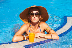 Beautiful blonde woman wearing a hat and sunglasses, enjoying th Stock Photos