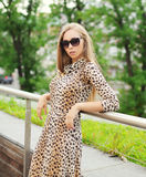 Beautiful blonde woman wearing a leopard dress and sunglasses Stock Image