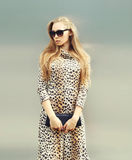 Beautiful blonde woman wearing a leopard dress and sunglasses with handbag clutch in city Royalty Free Stock Photography