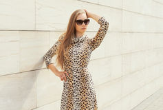 Beautiful blonde woman wearing a leopard dress and sunglasses Stock Images