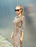 Beautiful blonde woman wearing a leopard dress and sunglasses posing in city Royalty Free Stock Photo