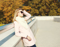 Beautiful blonde woman wearing a pink coat in autumn Royalty Free Stock Photo