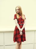 Beautiful blonde woman wearing red checkered dress Royalty Free Stock Photo