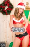 Beautiful blonde woman wearing santa claus clothes. In her wood house Stock Photos