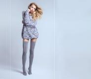 Beautiful blonde woman wearing stockings. Fashion photo of beautiful blonde woman with long slim legs posing in studio. Girl with long curly hair. Closed eyes Stock Photos