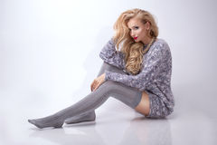 Beautiful blonde woman wearing stockings. Smiling beautiful blonde woman sitting on the floor. Fashionable young girl Stock Photos