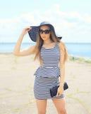 Beautiful blonde woman wearing a striped dress, straw hat Royalty Free Stock Photo