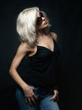 Beautiful blonde woman wearing sunglasses posing over black back. Ground. Model tests. Fun fashion studio shot Stock Image