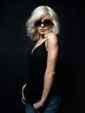 Beautiful blonde woman wearing sunglasses posing over black back. Ground. Model tests. Fun fashion studio shot Stock Photos