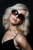 Beautiful blonde woman wearing sunglasses. Posing over black background. Model tests. Fashion studio shot Royalty Free Stock Image