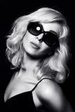 Beautiful blonde woman wearing sunglasses. Posing over black background. Model tests. Fun fashion studio shot. Black and white photo Stock Image