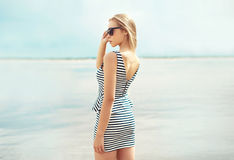 Beautiful blonde woman wearing a sunglasses and striped dress. Standing in profile looking on the sea Stock Photography
