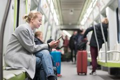 Beautiful blonde woman wearing winter coat reading on the phone while traveling by metro public transport. stock photos