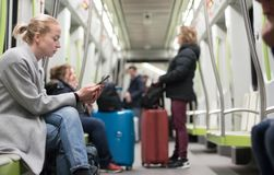 Beautiful blonde woman wearing winter coat reading on the phone while traveling by metro public transport. stock photo