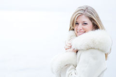 Beautiful blonde woman in white fur coat. Beautiful blonde woman with green eyes wears a white fur coat Stock Photos