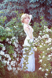 Beautiful blonde woman in white sundress posing in garden Stock Photos