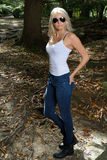 Beautiful blonde woman in white tank and jeans - in woods Royalty Free Stock Photos