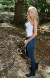 Beautiful blonde woman in white tank and jeans - in woods Royalty Free Stock Image