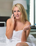 Beautiful blonde woman in white towel brushing teeth Royalty Free Stock Photos