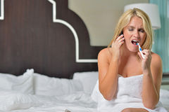 Beautiful blonde woman in white towel brushing teeth Royalty Free Stock Image