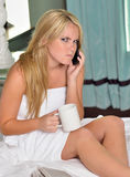 Beautiful blonde woman in white towel with coffee and phone Royalty Free Stock Image