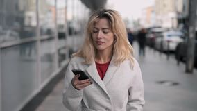 Beautiful blonde woman in white walking, smiling and web surfing. Attractive blonde woman wearing white coat walking in autumn street, smiling and web surfing on stock video footage