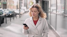 Beautiful blonde woman in white walking and web surfing. Attractive blonde woman wearing white coat walking in autumn street and web surfing on her smartphone stock video