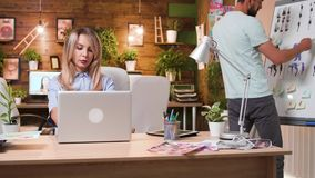 Beautiful blonde woman working on her computer in a professional creative workplace. Multimedia company stock footage