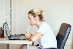 Beautiful blonde woman working on laptop at home. She is thoughtful and focused on work. Freelance, work at home concept. stock photo