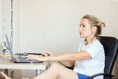 Beautiful blonde woman working on laptop at home. She is thoughtful and focused on work. Freelance, work at home concept. royalty free stock images