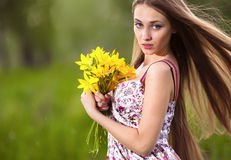 Beautiful blonde woman with yellow flowers outdoor Stock Photo