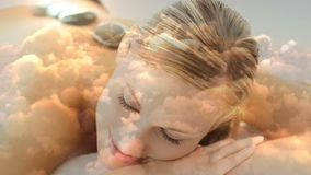 Beautiful blonde women lying at spa with hot basalt stone on the back and cloudscape for valentine d. Ay 4k stock video