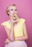 Beautiful blonde women with yellow blouse taste yellow dessert. Fashion shot. Soft colors Stock Photography