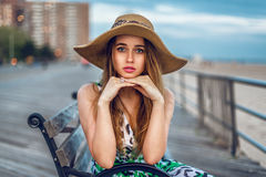 Beautiful blonde young adult woman sitting on the bench wearing hat near ocean beach shore. Girl looking into the camera in city Stock Photography